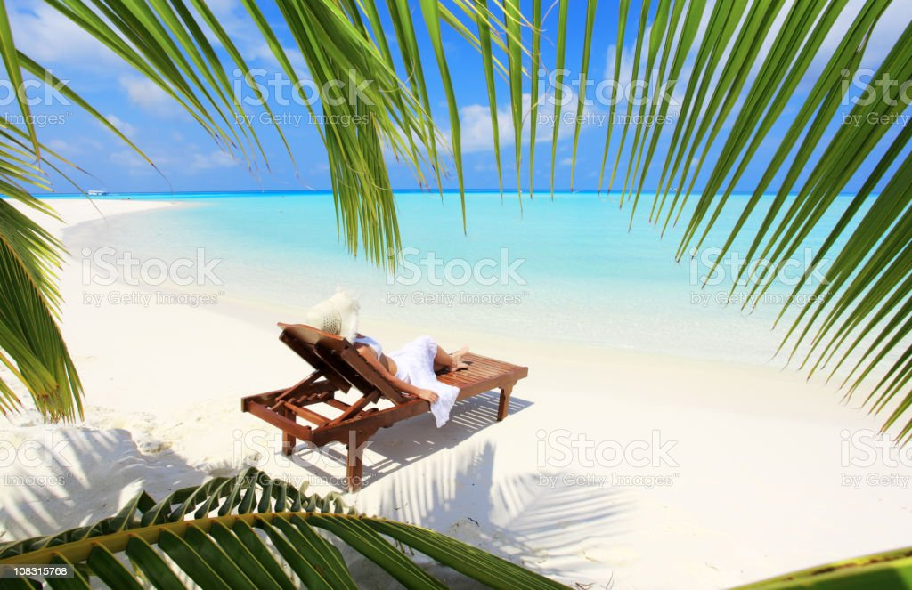View through palm leaves at woman an deck chair. royalty-free stock photo