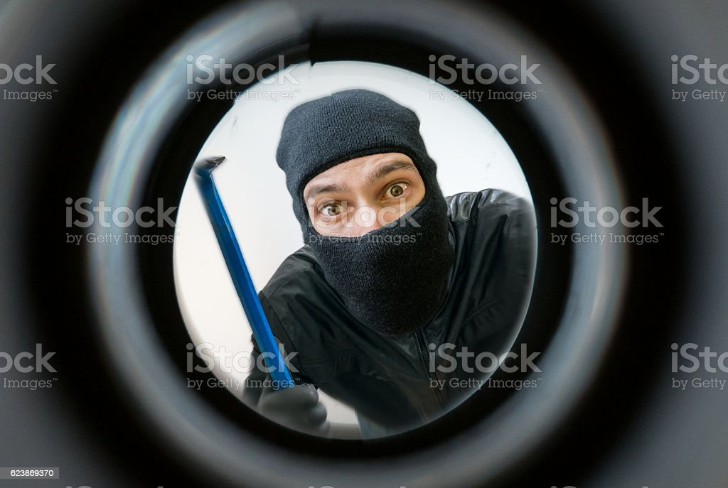 View through peephole. Thief masked with balaclava is behind door. stock photo