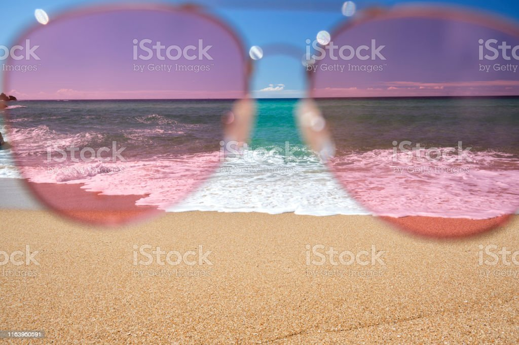 view through Pink lens sunglasses of blue sky and sea on a bright...