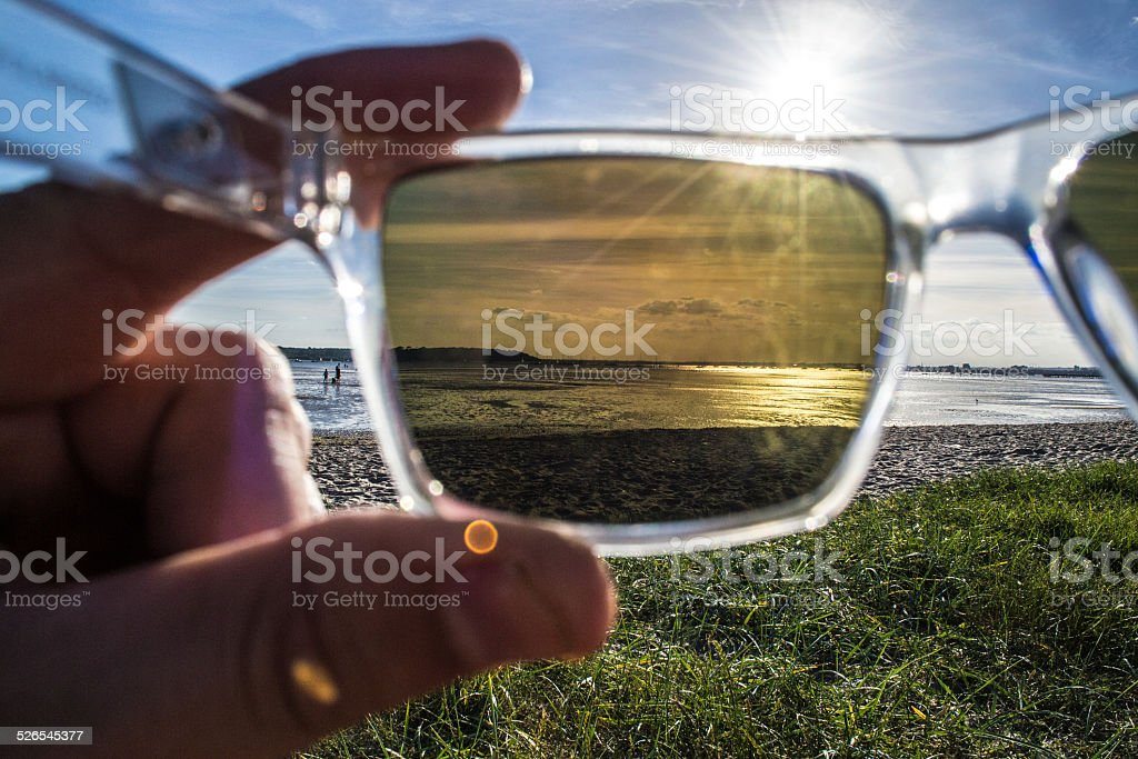 View through polarized sunglasses of harbour, ocean and beach stock photo