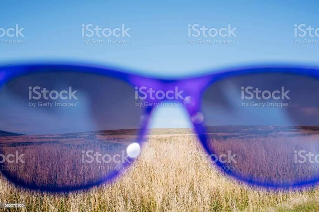view through sunglasses over a bright sunny hillside. royalty-free stock photo