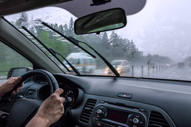 View through the rain-drenched windshield. Driver's hands and part of the car interior Blurred silhouettes of vehicles. Inside view of the car windshield wiper stock pictures, royalty-free photos & images