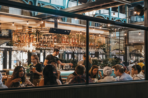 London, UK - August 31, 2019: View through the window of staff and customers inside Buns and Buns restaurant in Covent Garden Market, one of the most popular tourist sites in London, UK.