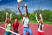 View through volleyball net of playing children trying to catch the ball on the playground during summer sunny day