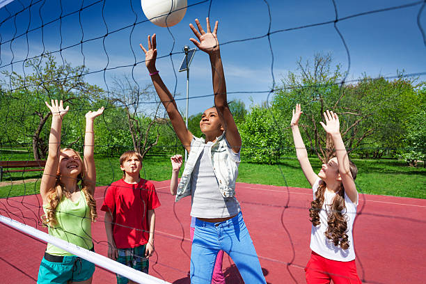 View through volleyball net of playing children stock photo