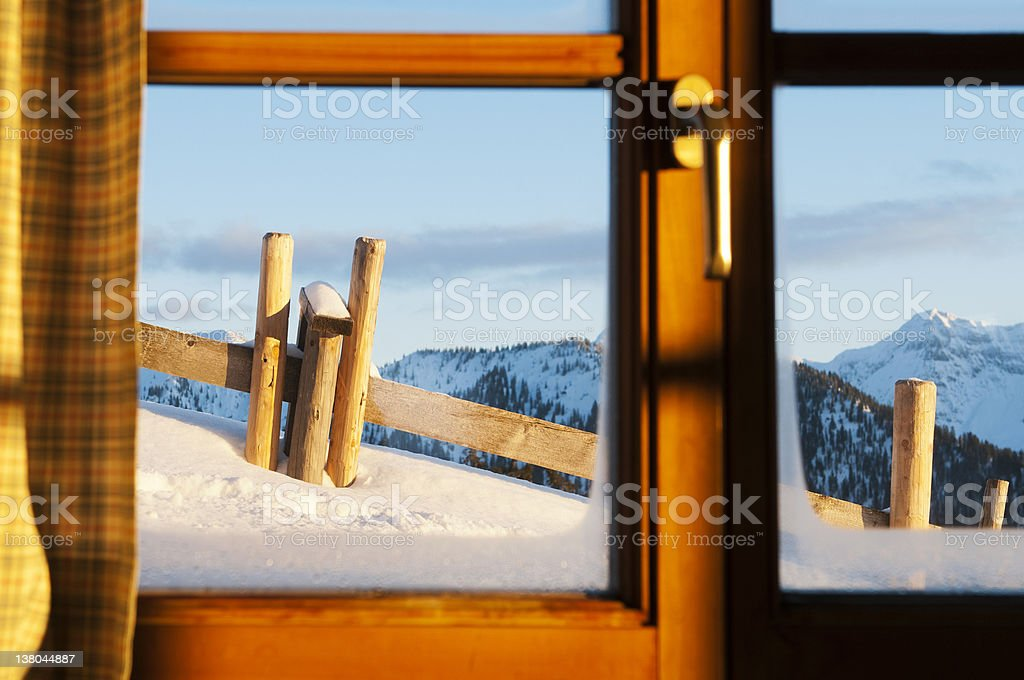 view through window of a chalet at tthe snowy landscape stock photo