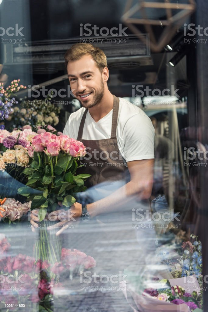View Through Window Of Handsome Florist Holding Bouquet Of