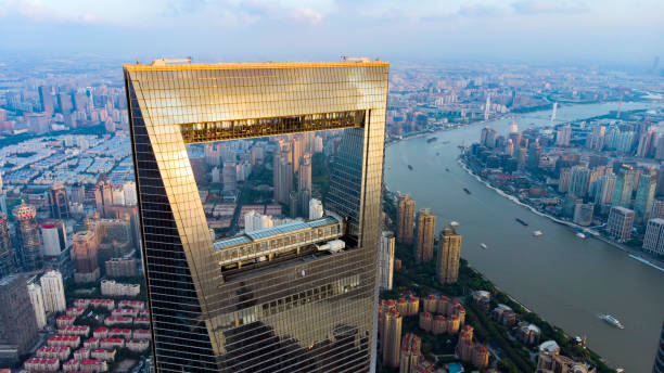 View Through Window Of Shanghai Skyscraper To Low Rise Residential District in Pudong. CHINA, SHANGHAI - AUGUST 4, 2018. View To Huangpu River And Cargo Shipping Boats And Shanghai World Financial Center. Window Of Shanghai Skyline And Opener. shanghai stock pictures, royalty-free photos & images