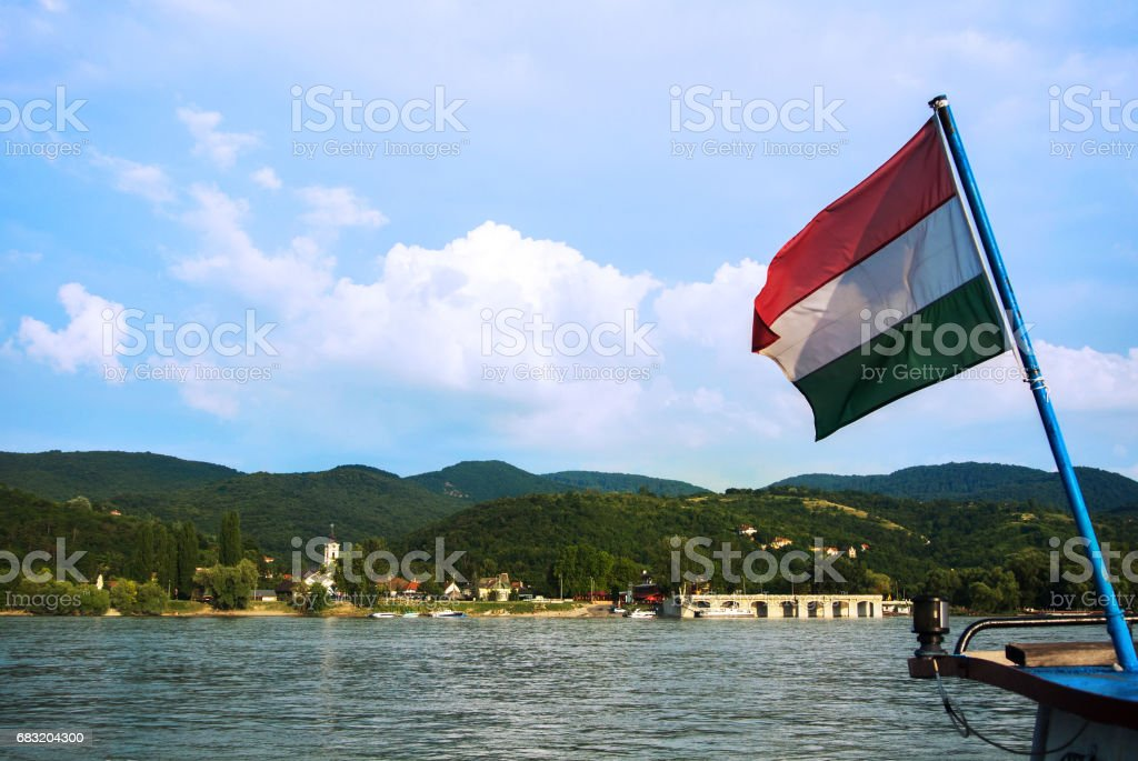 A view to a church at Visegrad, a small town at Hungary near Budapest from a ship at Danube, and a hungarian flag at the foreground. ロイヤリティフリーストックフォト