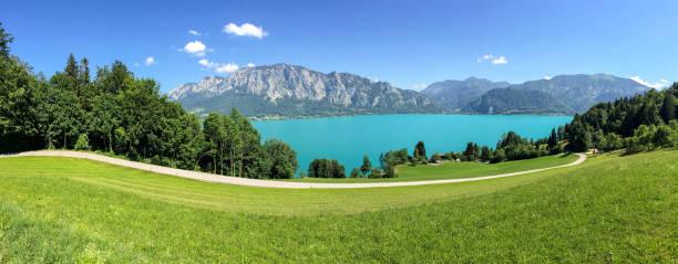 Vista para o lago Attersee com pastagens verdes prados e montanhas Alpes perto Nussdorf Salzburg, Áustria - foto de acervo