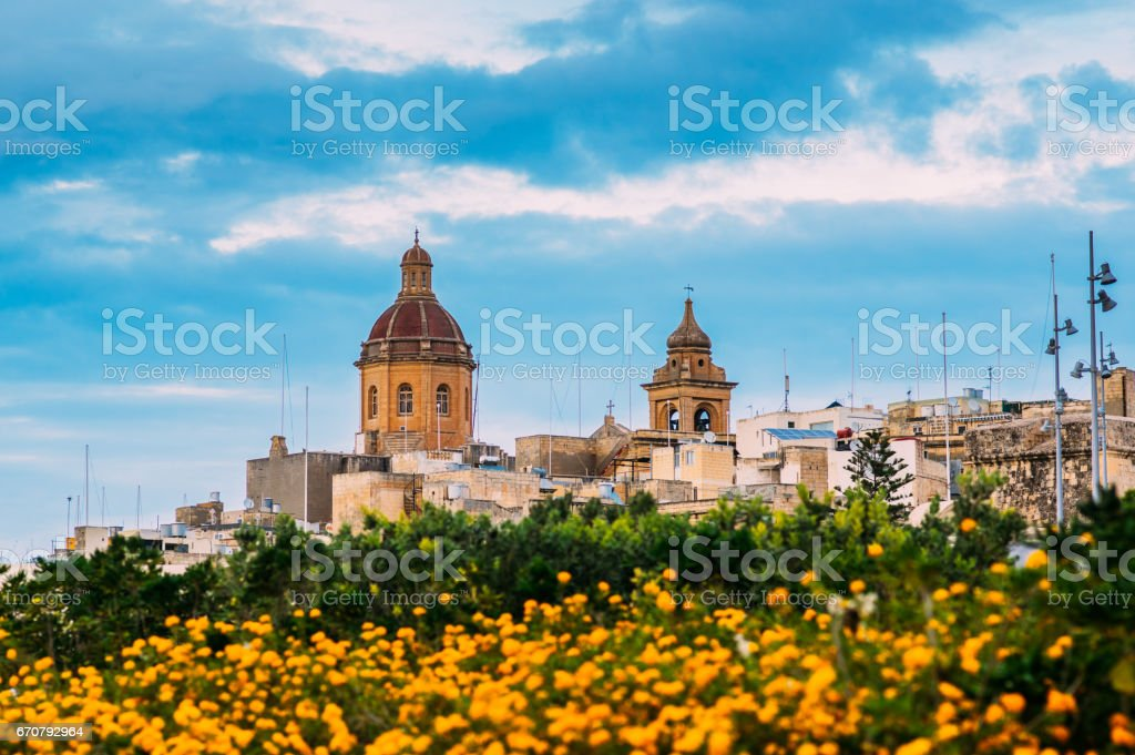 View to St. Lawrence's Church with orange flowers in Il-Birgu stock photo