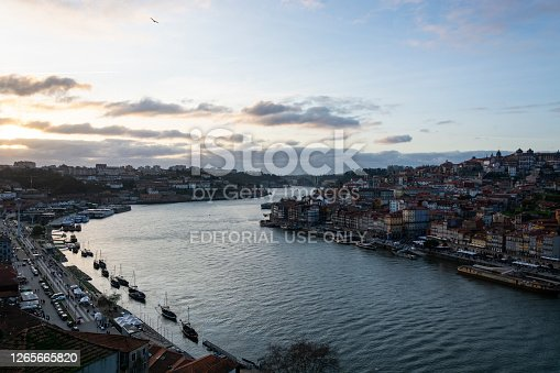 Porto, Portugal - 02/25/2020: View to the city of Porto (Portugal) and Douro river from D. Luis I bridge with cloudy sky, at sunset