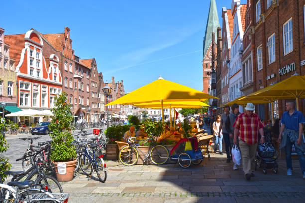 View to the German medieval town of Lueneburg. You see the facades of bricks and small shops, tourists and a lot of bikes. Lueneburg, Germany - June 5, 2018: View to the German medieval town of Lueneburg. You see the facades of bricks and small shops, tourists and a lot of bikes. lüneburg stock pictures, royalty-free photos & images