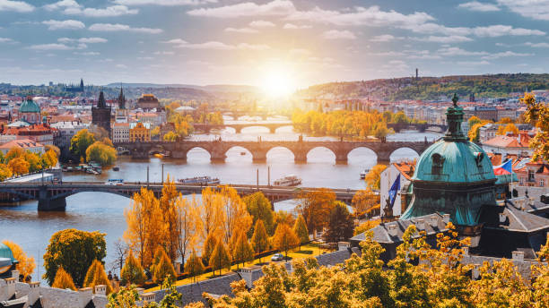 view to the historical bridges, prague old town and vltava river from popular view point in the letna park (letenske sady), beautiful autumn landscape in soft yellow light, czech republic - чехия стоковые фото и изображения