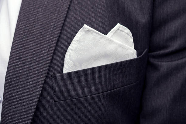 View to the male coat pocket with a fixed white square. Men's suit accessories. Wedding male guest's attire. Male wedding style. Formal dinner outfit for men. Elements of suit. Pocket square folding. stock photo