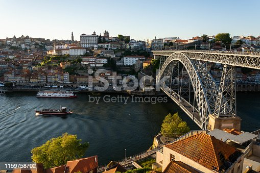 View to thef old Porto city: old colorful buildings with orange roofs and D. Luis bridge made of iron. Douro river with a boat.