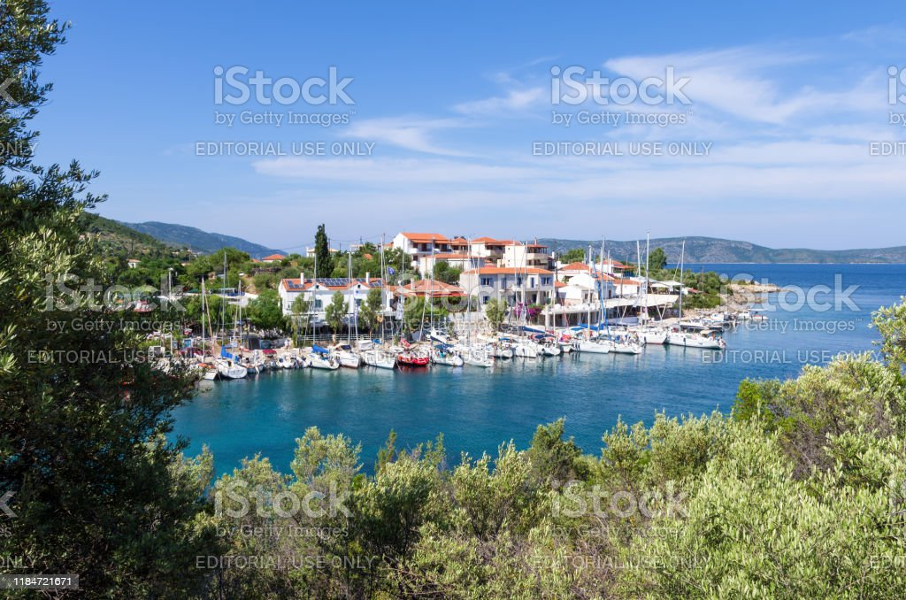 View to the picturesque little harbor of Steni Vala village, Alonnisos island, Greece June 15th 2019 - Steni Vala, Alonissos island, Greece - The picturesque little harbor of Steni Vala village, Alonnisos island, full of sailing yachts moored in front of the seaside taverns and cafeterias Alonissos Stock Photo
