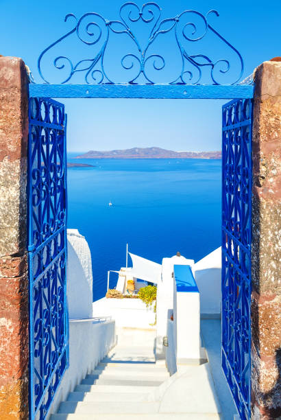 view to the sea and volcano through door, from fira the capital of santorini island in greece - santorini stock photos and pictures