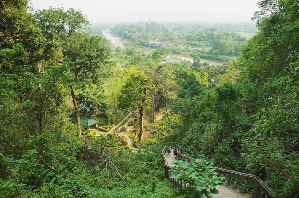 blick auf die stadt von vang vieng mit der hängebrücke über nam song river aus dem kalkstein karst-gebirge in vang vieng, laos. - vang vieng stock-fotos und bilder