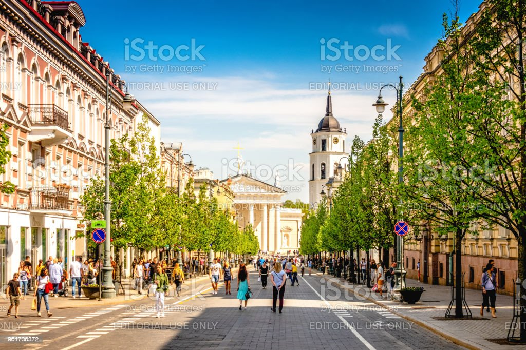 Vilnius, Lithuania - May 1, 2018: View to Vilnius city street -Gedimino avenue, Vilnius Cathedral and bell tower with people walking and riding bike in sunny day. royalty-free stock photo