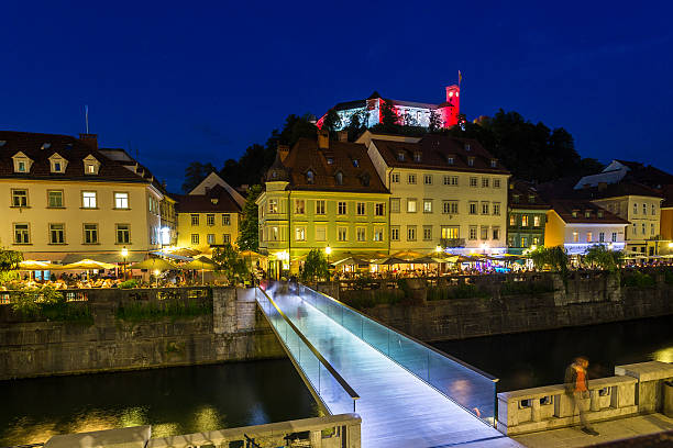 View towards Ljubljana Castle at night Ljubljana, Slovenia - May 26, 2016: A view towards Ljubljana Castle at night. A bridge, buildings and people can be seen. ljubljana castle stock pictures, royalty-free photos & images