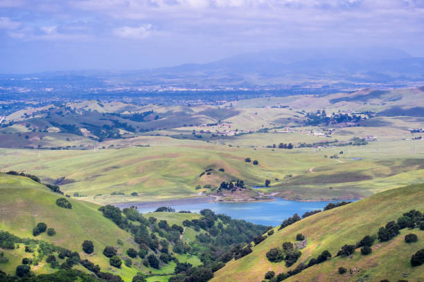 View towards San Antonio reservoir surrounded green hills; Pleasanton and Mt Diablo in the background, Alameda county, San Francisco bay area, California View towards San Antonio reservoir surrounded green hills; Pleasanton and Mt Diablo in the background, Alameda county, San Francisco bay area, California alameda california stock pictures, royalty-free photos & images
