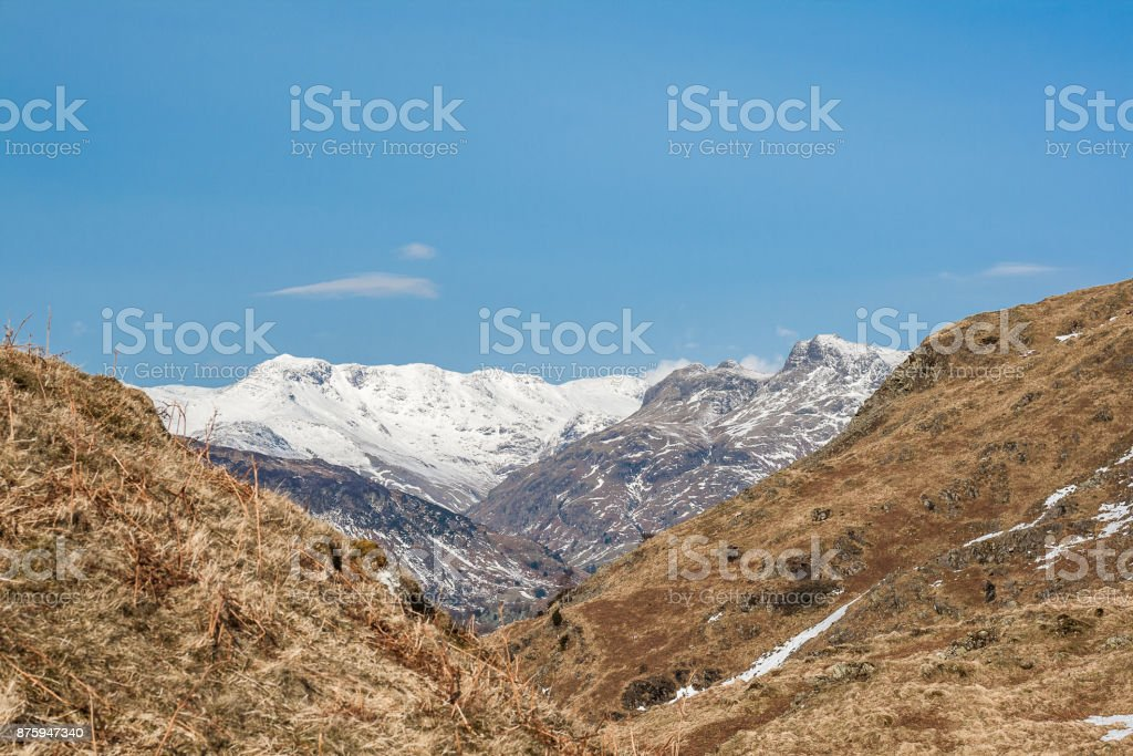 View towards snowy Langdale mountains in Lake District from Loughrigg stock photo