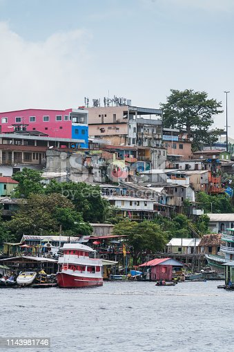View from the river Rio Negro with different passenger ferries, normal residential buildings and favelas in the  city of Manaus
