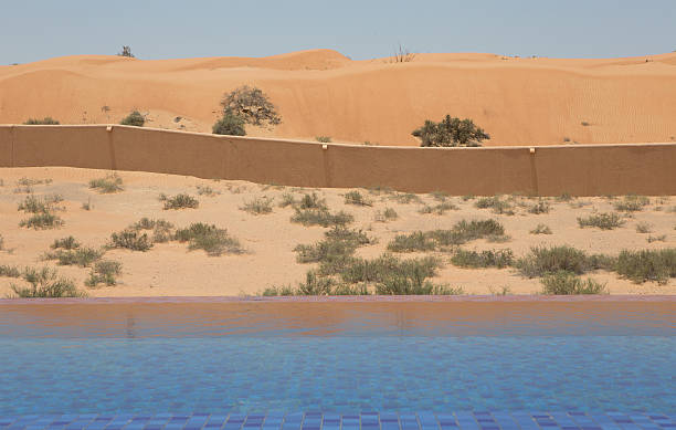 view towards the desert from an infinity pool, wadi khadeja. - perpetual motion stock photos and pictures