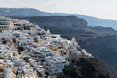 View towards Thira from distance. Different dwellings can be seen on the sloped city on the hills