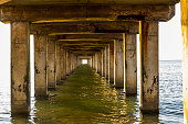View under a long wooden pier with pillars standing in the water