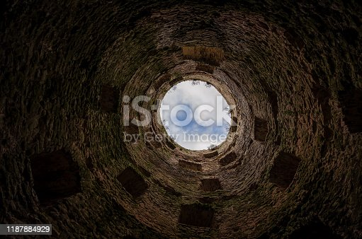 View up inside an old round fortress tower. Visible medieval brickwork and windows at different levels. In the background, a fragment of the sky with clouds is visible. Background.