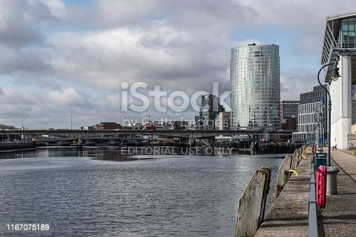 Belfast, United Kingdom - August 7, 2019: View upstream along the River Lagan from Belfast's harbour development (a redeveloped area of Class A offices, public squares, hotels and apartments) towards the city centre.  The bridge carries the M3 motorway across the river.  The tall, curve high rise building to the right hand side is the Obel Tower, Belfast's tallest building.  Constructed in 2006, to the designs of Broadway Malyan and Chris Marshall, it is a mixed use development of Class A office space and residential apartments.