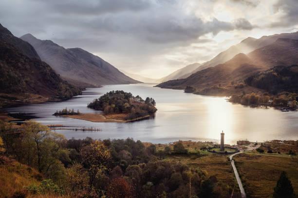 blick auf den berühmten schottischen see loch shiel mit glenfinnan-denkmal bei sonnenuntergang - schottische kultur stock-fotos und bilder