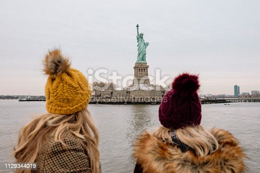 Two women viewing the Statue of Liberty from a tour boat in New York City.