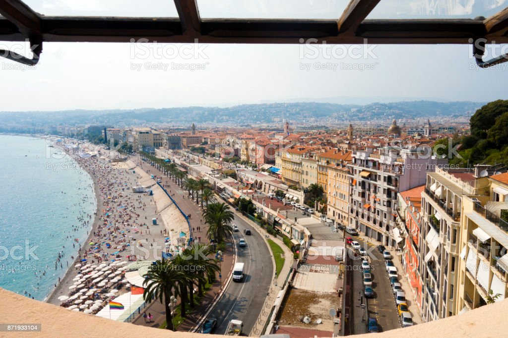 Viewpoint overlooking blue mediterranean sea beach with palm trees and bright and colorful city of Nice France on sunny day in Cote d-Azure stock photo