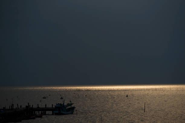 blick auf das meer sonnenlicht trifft die wasseroberfläche bei sonnenuntergang. - moo stock-fotos und bilder
