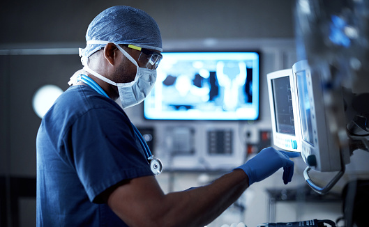 Shot of a surgeon looking at a monitor in an operating room