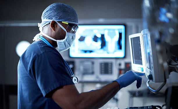 Vigilantly monitoring his patient's vitals Shot of a surgeon looking at a monitor in an operating room medical equipment stock pictures, royalty-free photos & images