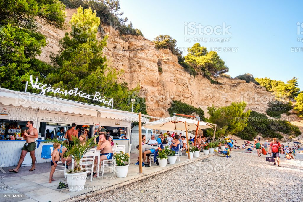 Vignanotica beach bar, tourists in the famous Gargano beach of vignanotica - foto stock
