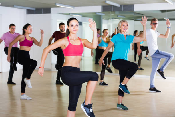 vigorous men and ladies dancing aerobics at lesson - aerobics stock photos and pictures