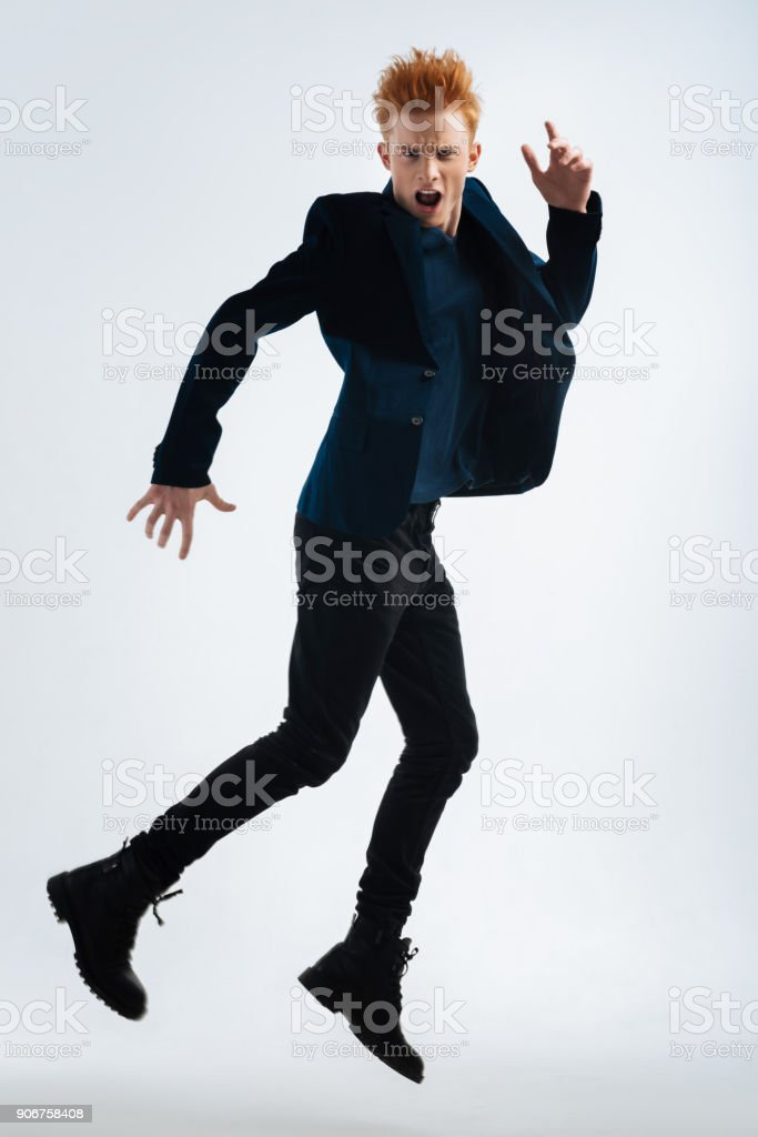 Vigorous young man shouting and jumping stock photo