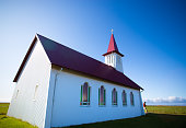 Vik, Iceland: Man at Red and White Sunlit Church (Reyniskirkja), Blue Sky Background.