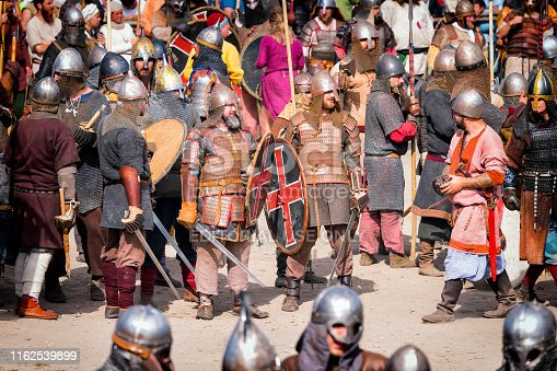 Wolin, Poland - August 05, 2018:Reenactors dressed in Viking and Slav armor uniforms stand in battle array and prepare to battle which takes place at the ending of the annual the Wolin Viking Festival, Poland. Wolin Viking Festival is an important meeting point for Viking and Slav reenactors of Europe.