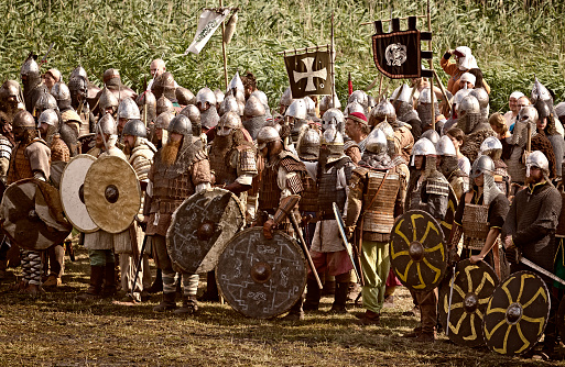 Wolin, Poland - August 03, 2014:Reenactors dressed in Viking and Slav armor uniforms stand in battle array and prepare to battle which takes place at the ending of the annual the Wolin Viking Festival, Poland. Wolin Viking Festival is an important meeting point for Viking and Slav reenactors of Europe.