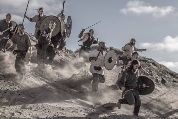 Viking Group A hoard of Weapon wielding viking warriors on a sandy battlefield dune battlefield stock pictures, royalty-free photos & images