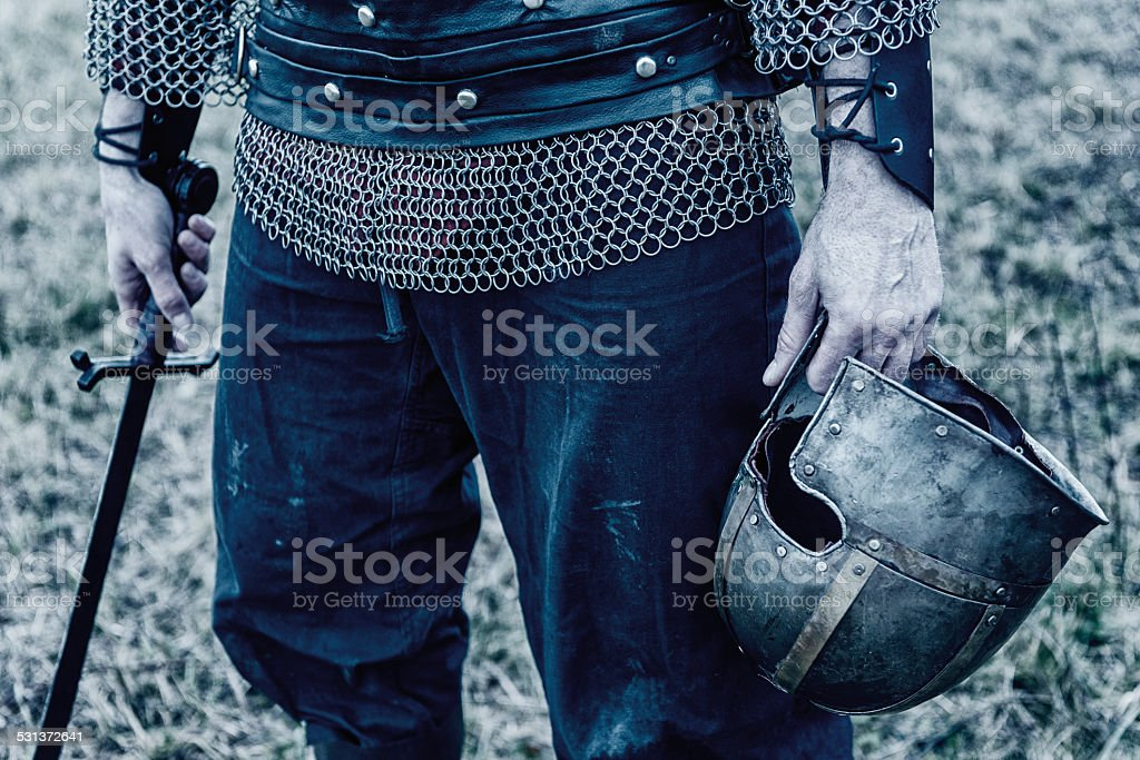 Viking or knight holds a helmet and sword stock photo