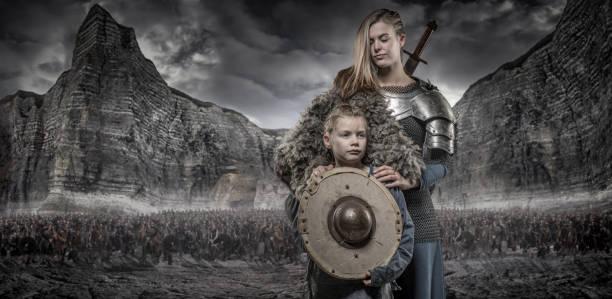 wikinger-krieger-königin und prinzessin vor viking hort und gebirge - filmplakate stock-fotos und bilder