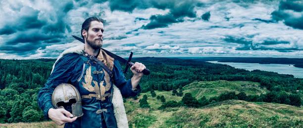 wikinger-krieger steht auf dem hügel mit blick auf die landschaft - mittelalterliche ritter stock-fotos und bilder