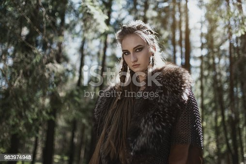 istock Viking woman wearing traditional warrior clothes in a deep mysterious forest. 983974948